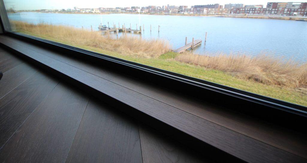 Vloerenhuis Amsterdam is dealer van het Zwitserse merk Bauwerk. Dit topproduct heeft de meeste strakke pasvorm die denkbaar is en heeft de mooiste kleur afwerkingen. Hier ziet u een kerngerookte houten vloer op vloerverwarming met een afwerking bij het grote raamkozijn.