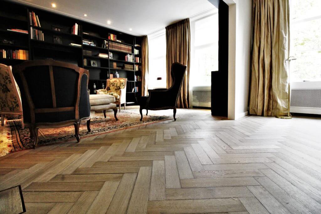 Grigio verouderde visgraatvloeren gelegd in massief eikenhout , gespijkerd en verlijmd op de houten ondervloer. Deze zogeheten Tapis vloer ligt in Amsterdam Zuid.