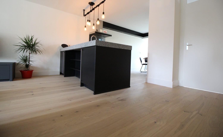 Een keukeneiland of keukenblok op een houten vloer is hier te zien op een vloer van Bauwerk parket in Amsterdam, natuurlijk bij Vloerenhuis Amsterdam.