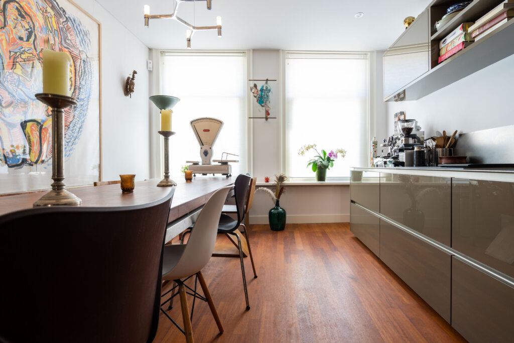 Strakke designkeuken met een Afzelia Doussie strokenvloer op vloerverwarming in Amsterdam